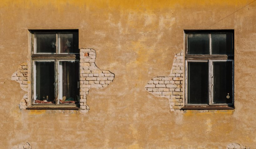 two windows on a roughed up wall