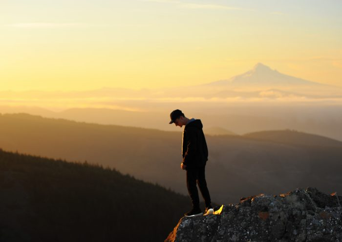 man looking down a mountain top
